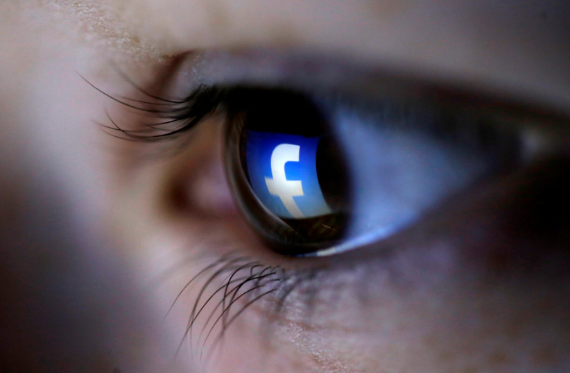 A picture illustration shows a Facebook logo reflected in a person's eye (photo credit: REUTERS/DADO RUVIC/ILLUSTRATION/FILE PHOTO)