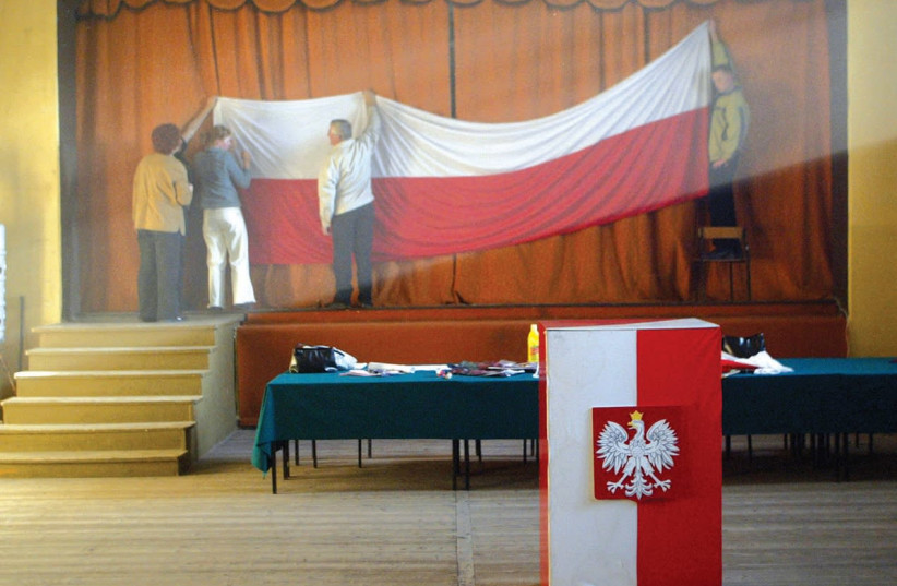 MEN PUT up a Polish flag at an election booth. The country is struggling with its past. (photo credit: REUTERS)