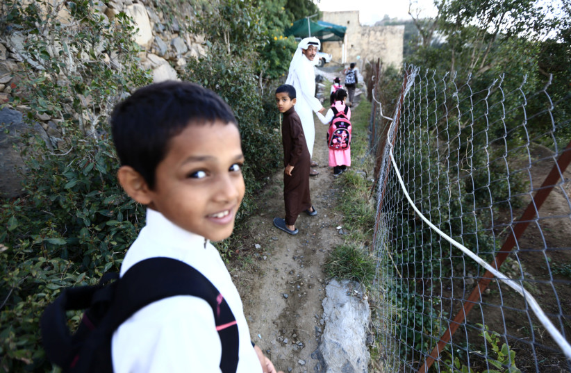 Saudi man Yazid al-Fefi walks with his children as they make their way to their schools through Fifa Mountain, in Jazan, south of Saudi Arabia, December 15, 2016. Picture take December 15, 2016.   (photo credit: MOHAMED AL HWAITY/REUTERS)