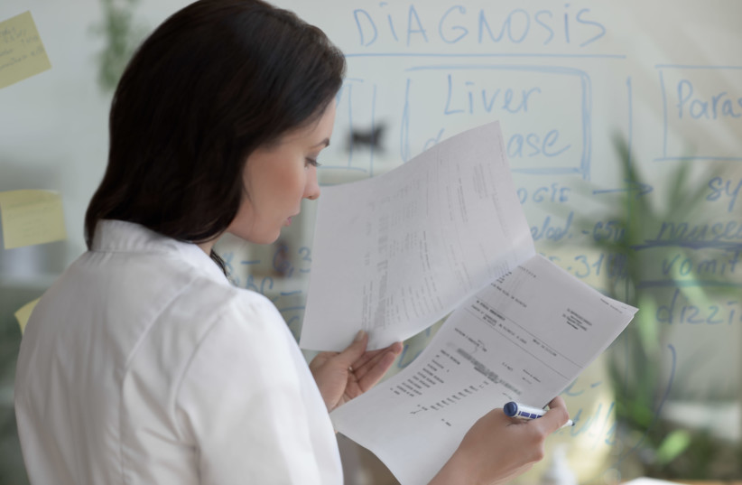 A doctor examines patient medical records. [Illustrative] (photo credit: INGIMAGE)