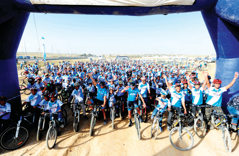 Over 500 children from the Beduin village of Wadi al-Na'am were treated to an event arranged by the Israel Cycling Academy, receiving bikes and racing shirts while taking part in a five-kilometer course with riders from ICA 's development team. (photo credit: VELOIMAGES/COURTESY)