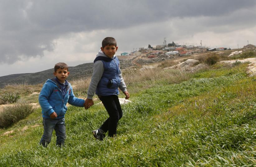 Palestinian boys walk near Jewish settlements in the West Bank village of Jaloud near Nablus (photo credit: ABED OMAR QUSINI/REUTERS)