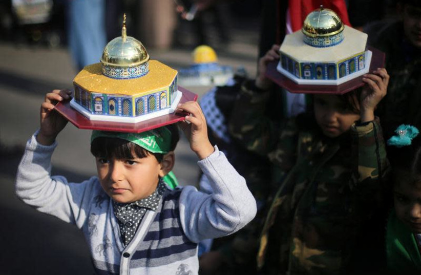 Palestinian children hold models depicting the Dome of the Rock during a protest against U.S. President Donald Trump's decision to recognize Jerusalem as the capital of Israel, near the central Gaza Strip December 15, 2017 (photo credit: IBRAHEEM ABU MUSTAFA / REUTERS)