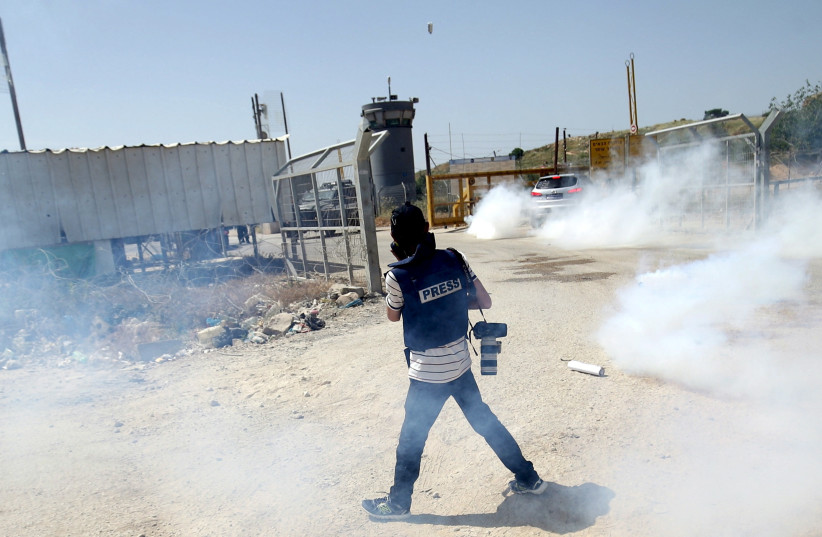 A journalist at a demonstration in Ramallah (photo credit: MOHAMAD TOROKMAN/REUTERS)