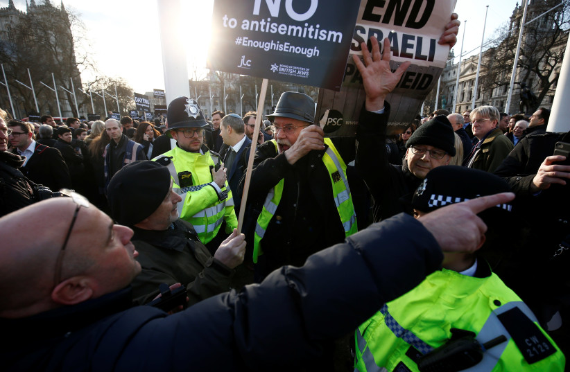Protesters hold placards and flags during a demonstration opposing antisemitism, in Parliament Square in London, Britain, March 26, 2018.  (photo credit: REUTERS)