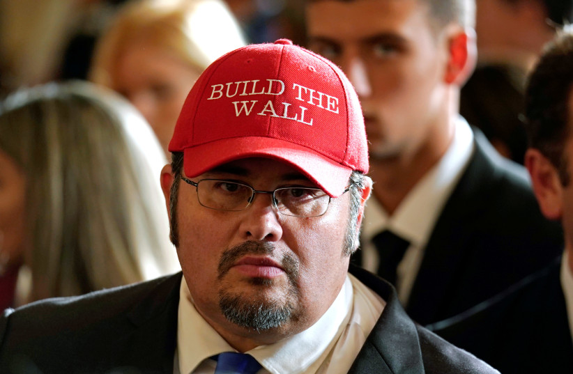 """Virginia Republican party leader Fredy Burgos wearing a """"Build the Wall"""" hat at an event to commemorate Hispanic Heritage Month hosted by US President Donald Trump at the White House in Washington (photo credit: KEVIN LAMARQUE/REUTERS)"""