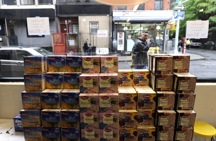 Packages of Passover Matzos sit in the window of a store on the lower east side of New York  (photo credit: TIMOTHY A. CLARY / AFP)