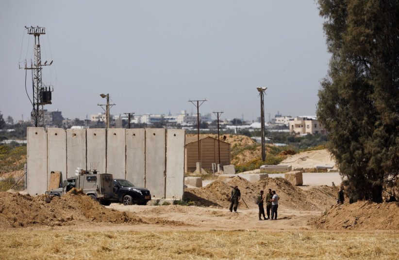 Israeli soldiers stand close to a security barrier near the border between Israel and the Gaza Strip, Israel March, 2018 (photo credit: AMIR COHEN/REUTERS)
