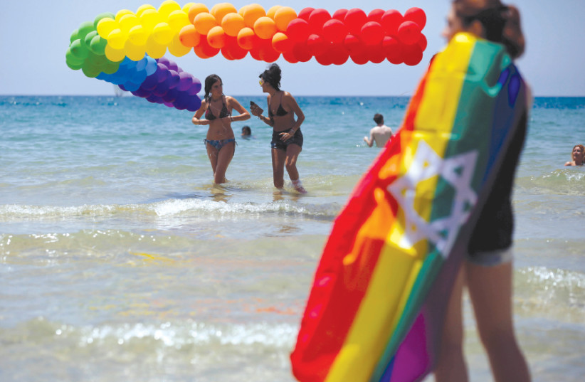 REVELERS DIP in the Mediterranean Sea as they take part in a Gay Pride parade in Tel Aviv last year (photo credit: AMIR COHEN/REUTERS)