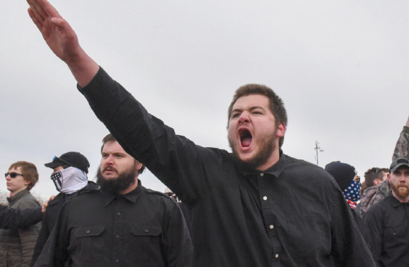 A MEMBER of a neo-Nazi party gives a salute outside a speech by Richard Spencer on the campus of Michigan State University on March 5 (photo credit: REUTERS/STEPHANIE KEITH)