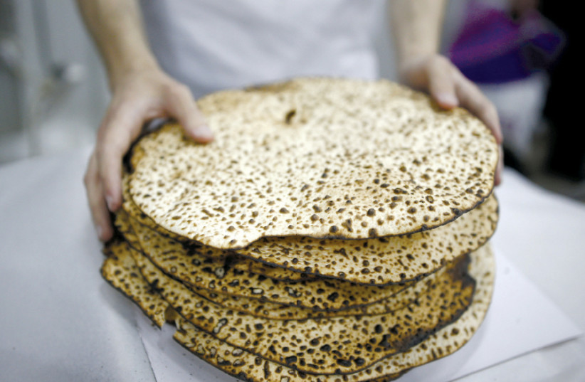 A MAN wraps fresh matza during Passover in Ashdod in 2016 (photo credit: AMIR COHEN/REUTERS)