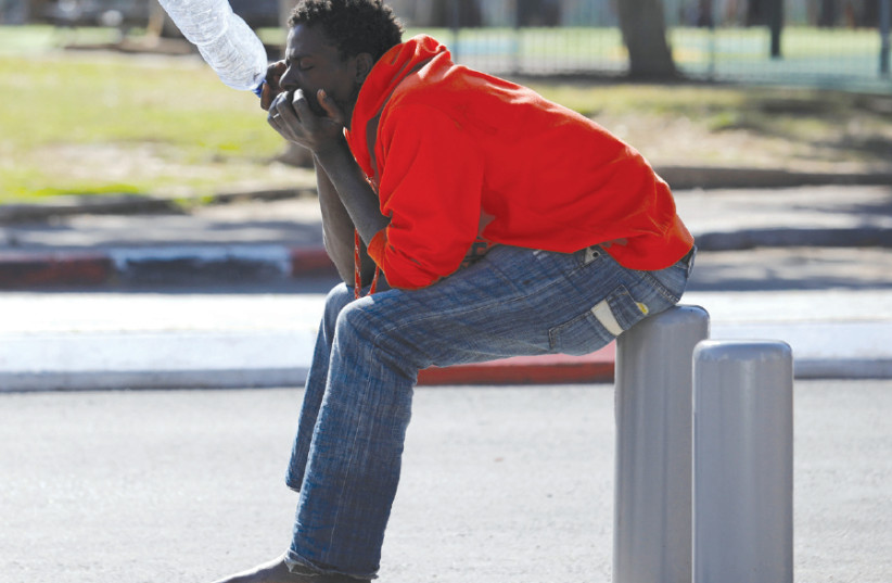 AN AFRICAN migrant sits on the street in Tel Aviv, earlier 2018 (photo credit: AMIR COHEN/REUTERS)
