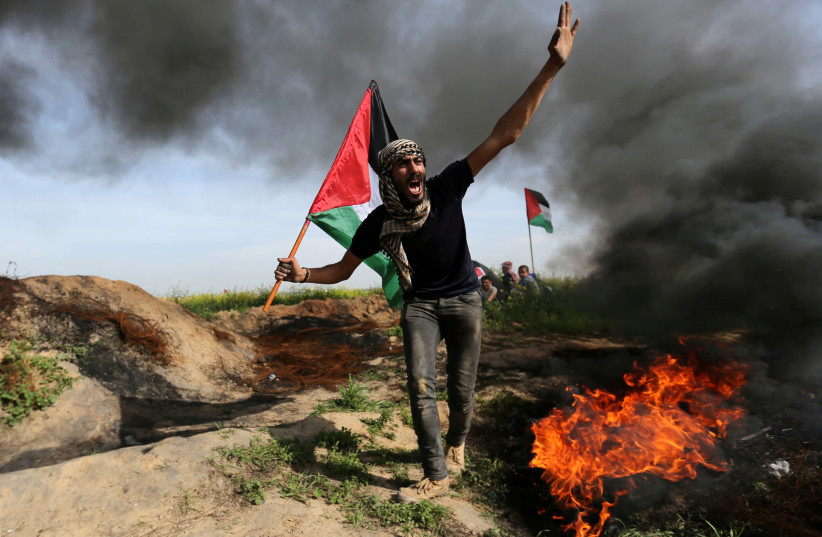 A demonstrator holds a Palestinian flag as he shouts during clashes with Israeli troops, near the border with Israel in the southern Gaza Strip March 2, 2018. (photo credit: IBRAHEEM ABU MUSTAFA / REUTERS)
