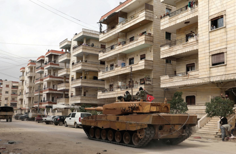 A Turkish tank rolls through the city of Afrin in northern Syria (photo credit: REUTERS)