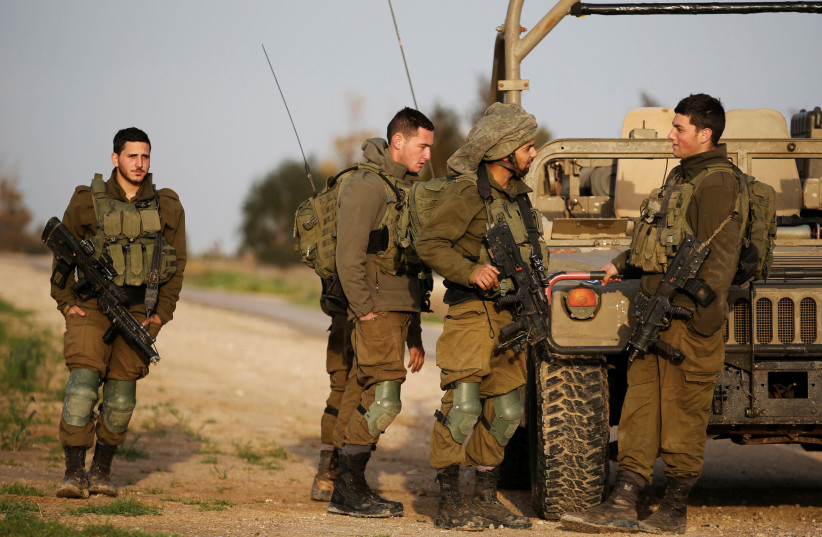 Israeli soldiers stands near a military jeep next to the border fence with the southern Gaza Strip near Kibbutz Nirim, Israel February 17, 2018.  (photo credit: REUTERS/AMIR COHEN)