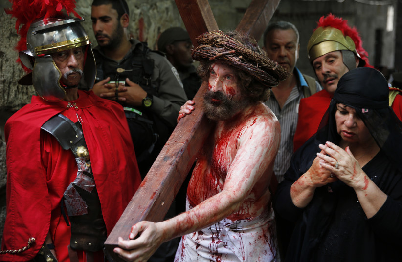 A man playing the role of Jesus carries a cross during a procession along the Via Dolorosa on Good Friday during Holy Week, in Jerusalem's Old City April 18, 2014. (photo credit: FINBARR O'REILLY / REUTERS)