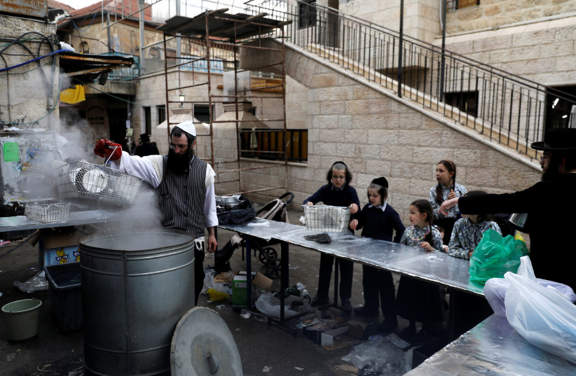 An ultra-Orthodox Jewish man dips cooking utensils in boiling water to remove remains of leaven in preparation for the upcoming Jewish holiday of Passover, in Jerusalem's Mea Shearim neighborhood, March 27, 2018. (photo credit: RONEN ZVULUN/REUTERS)
