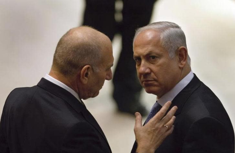 Incoming Israeli Prime Minister Benjamin Netanyahu (R) and outgoing Prime Minister Ehud Olmert speak on the plenum floor at the start of the swearing-in ceremony for Netanyahu's new government at parliament in Jerusalem March 31, 2009 (photo credit: DAVID SILVERMAN / REUTERS)