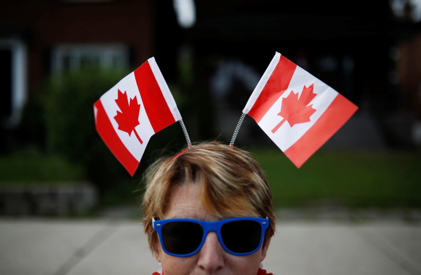 A woman wears Canadian flags on her head during the East York Toronto Canada Day parade, July 1, 2017 (photo credit: REUTERS/MARK BLINCH)