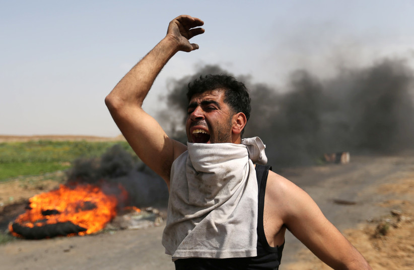 A Palestinian shouts during clashes along the Israel border with Gaza ahead of a protest in the southern Gaza Strip March 29, 2018. (photo credit: REUTERS/IBRAHEEM ABU MUSTAFA)