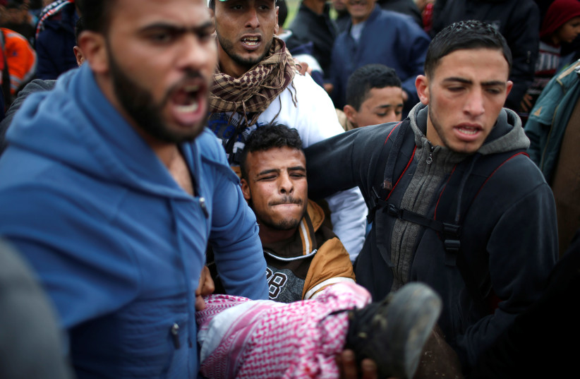 A wounded Palestinian is evacuated during clashes during a protest along the Israel border with Gaza, east of Gaza City March 30, 2018.  (photo credit: REUTERS/MOHAMMED SALEM)