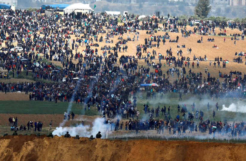 Israeli soldiers shoot tear gas from the Israeli side of the Israel-Gaza border, as Palestinians protest on the Gaza side of the border, March 30, 2018. (photo credit: AMIR COHEN/REUTERS)