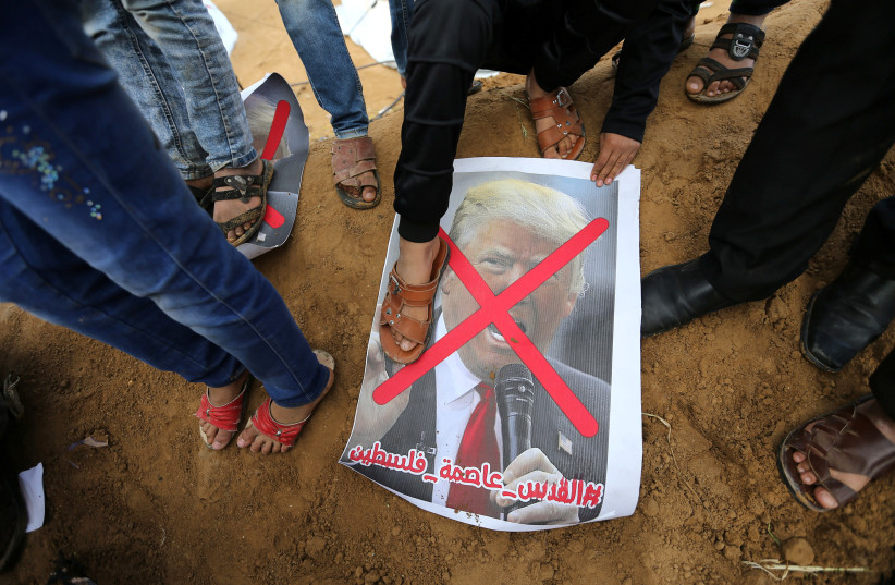 A Palestinian steps on a poster depicting U.S. President Donald Trump during a tent city protest along the Israel border with Gaza, demanding the right to return to their homeland, in the southern Gaza Strip March 30, 2018 (photo credit: IBRAHEEM ABU MUSTAFA / REUTERS)