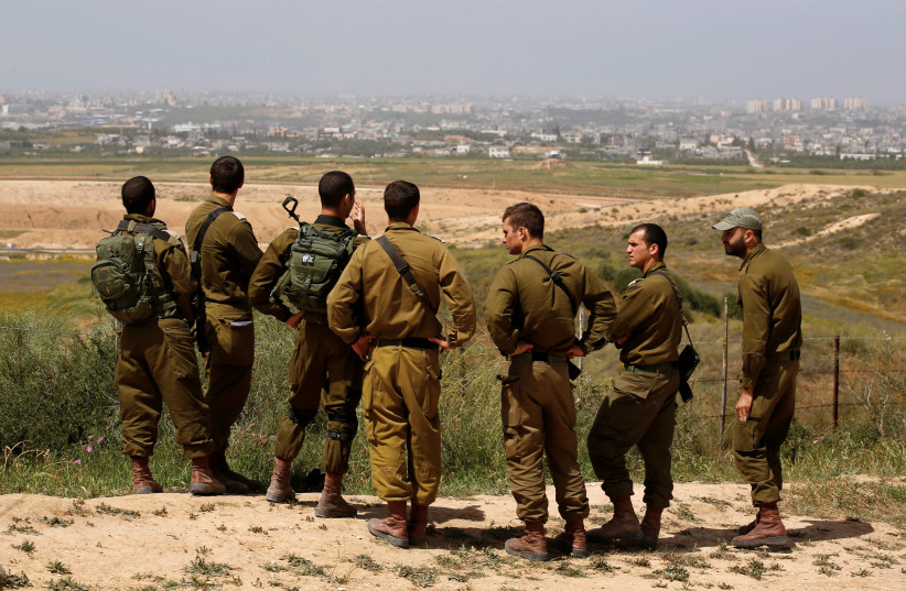 Israeli soldiers listen to a briefing on the Israeli side of the border with the northern Gaza Strip, Israel, March 29, 2018. (photo credit: AMIR COHEN/REUTERS)