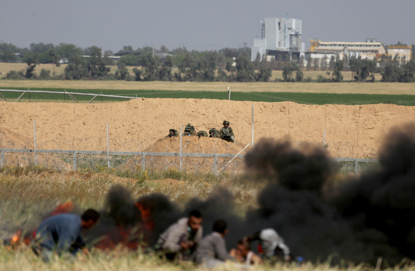 Palestinians take cover from Israeli snipers during clashes at the Gaza-Israel border at a protest in the southern Gaza Strip March 31, 2018 (photo credit: IBRAHEEM ABU MUSTAFA/REUTERS)