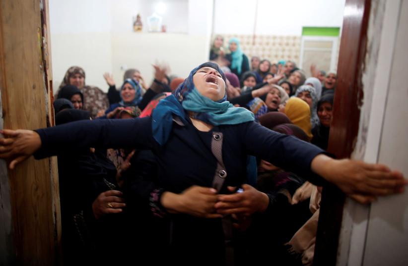 Mourners hold back a relative of Palestinian Hamdan Abu Amshah, who was killed along Israel border with Gaza (photo credit: REUTERS/SUHAIB SALEM)