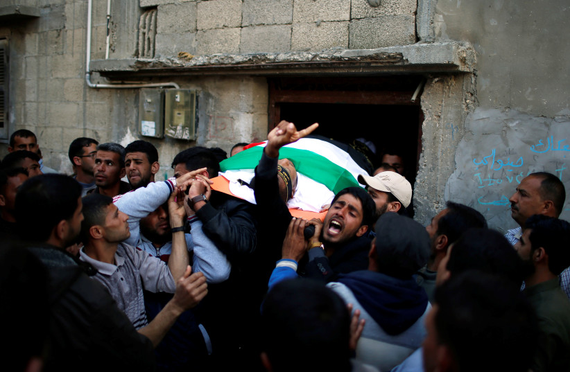 Mourners carry the body of Palestinian Faris al-Reqib, 29, who was killed during clashes at Israel-Gaza border, during his funeral in Khan Younis, in the southern Gaza Strip April 2, 2018. (photo credit: MOHAMMED SALEM/REUTERS)
