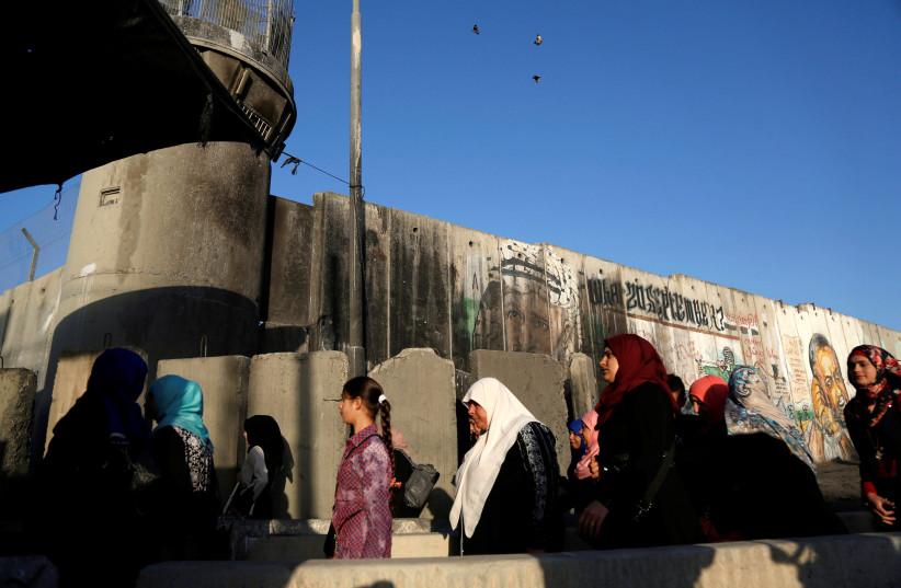 Palestinians wait to cross through Israeli Kalandiya checkpoint (photo credit: MOHAMAD TOROKMAN/REUTERS)