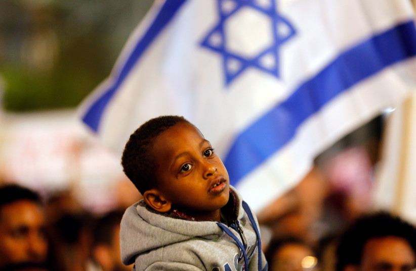 A boy takes part in a protest against the Israeli government's plan to deport African migrants, in Tel Aviv, Israel March 24, 2018. (photo credit: REUTERS/CORINNA KERN)