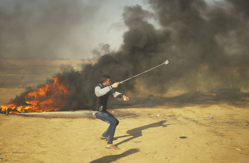 A Palestinian throws a rock towards Israeli forces on the Gaza border (photo credit: REUTERS)