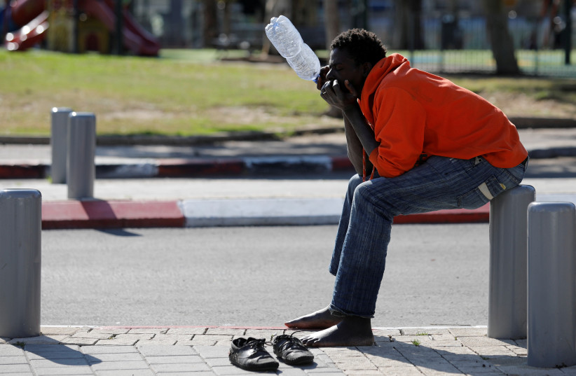 An African migrant sits on the street in Tel Aviv, Israel January 31, 2018. (photo credit: REUTERS/AMIR COHEN)