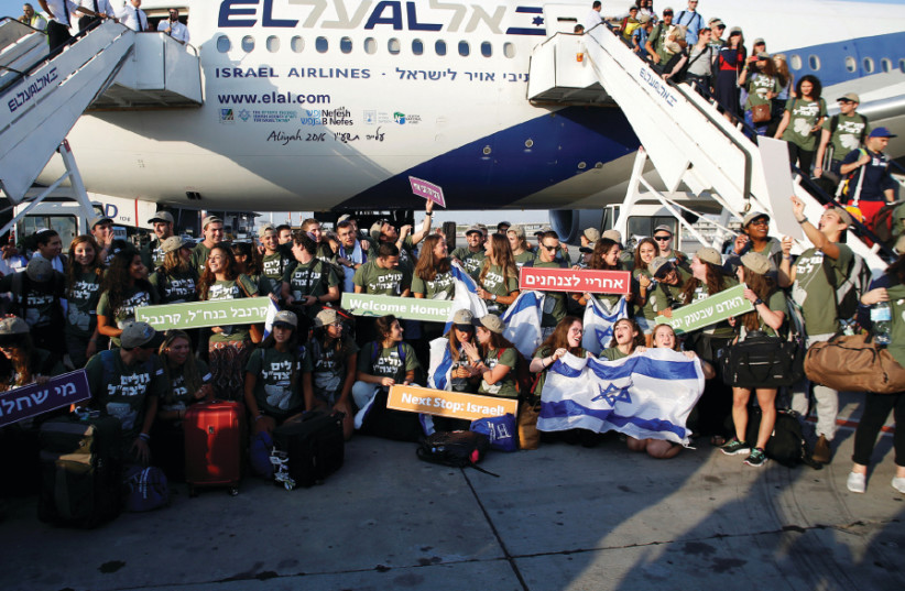 New immigrants from North America, including some 70 who will serve in the IDF, pose for a group picture upon landing in Israel on a special flight organized by Nefesh B'Nefesh (photo credit: BAZ RATNER/REUTERS)