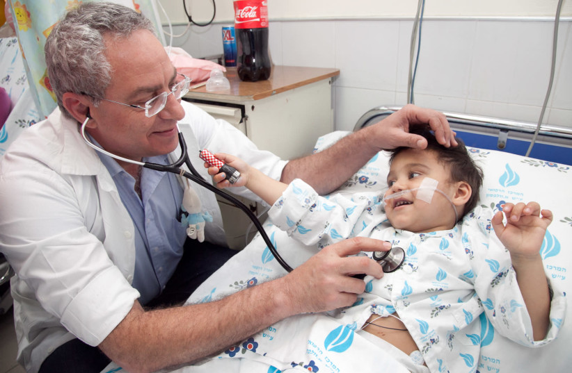 SACH courtesy photo shows Dr. Lior Sasson with child from Romania after undergoing surgery (photo credit: Courtesy)