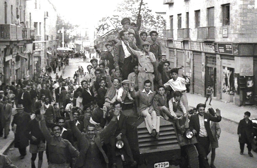 Crowds of people celebrate the founding of Israel in 1948. (photo credit: REUTERS)