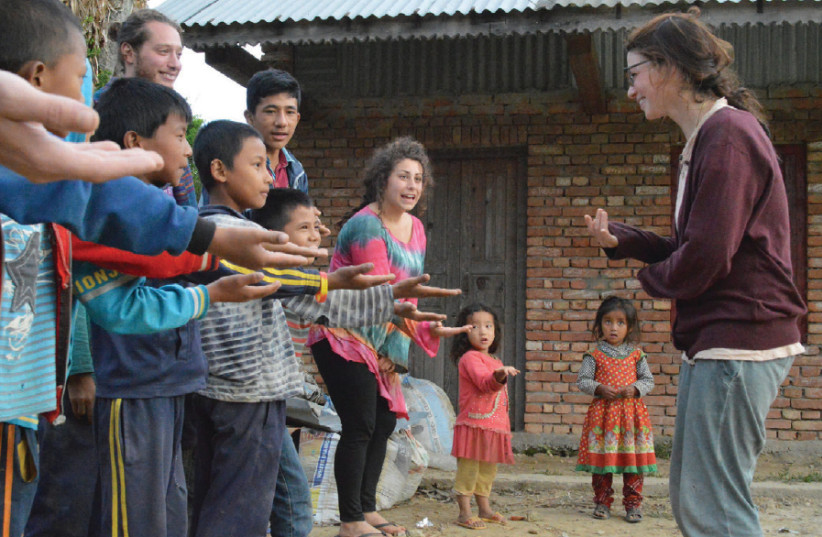 Volunteers in Manegau, the community that hosted the one-month volunteer program, run youth programs with the youth community mobilizer, Purna (photo credit: COURTESY TEVEL B'TZEDEK)