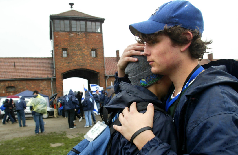 Two boys hug in front of the main railway building of the former Nazi death camp Birkenau (Auschwitz II) during the 'March of the Living' in Oswiecim, Poland (photo credit: KATARINA STOLTZ/ REUTERS)