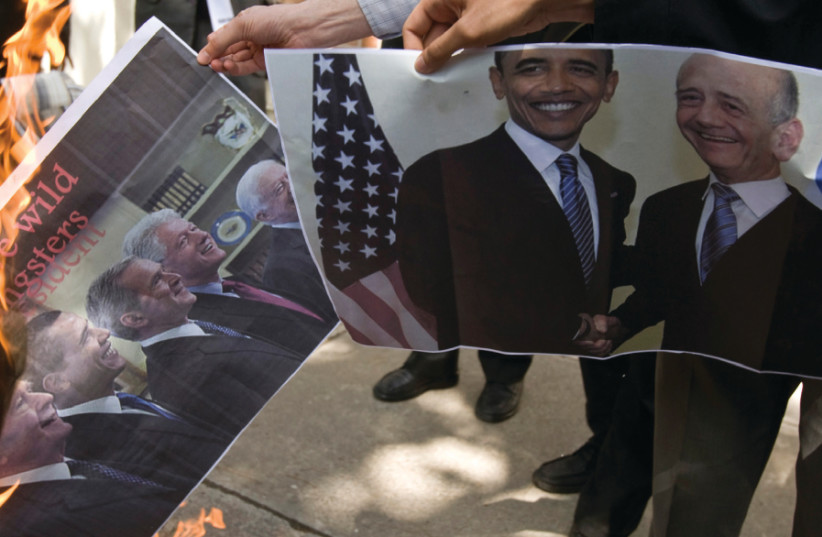 STUDENTS BURN a picture of former American presidents, along with another featuring Olmert (right) in front of the former US embassy in Tehran in 2009 (photo credit: REUTERS)