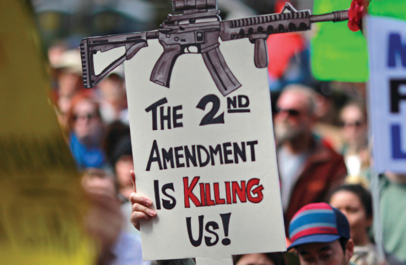 PROTESTERS HOLD signs during a 'March For Our Lives' demonstration demanding gun control in Sacramento, California, March 2018 (photo credit: BOB STRONG / REUTERS)