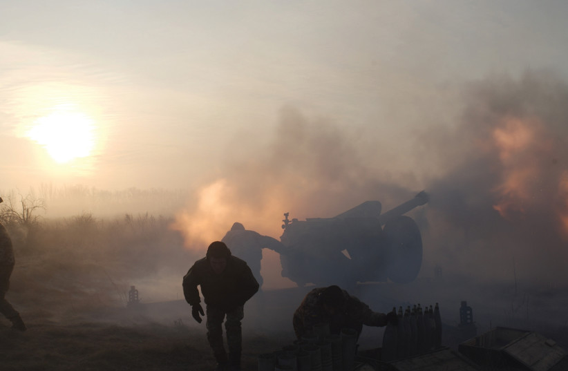 Ukrainian soldiers fire artillery during the conflict in Donbas (photo credit: REUTERS)