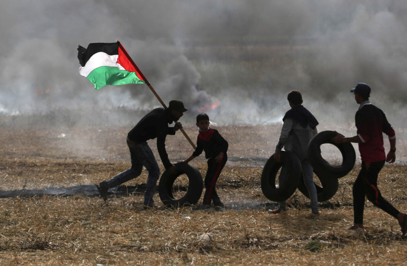 Palestinian protesters carry tires to burn them during clashes with Israeli troops at Israel-Gaza border, in the southern Gaza Strip April 5, 2018.  (photo credit: IBRAHEEM ABU MUSTAFA / REUTERS)