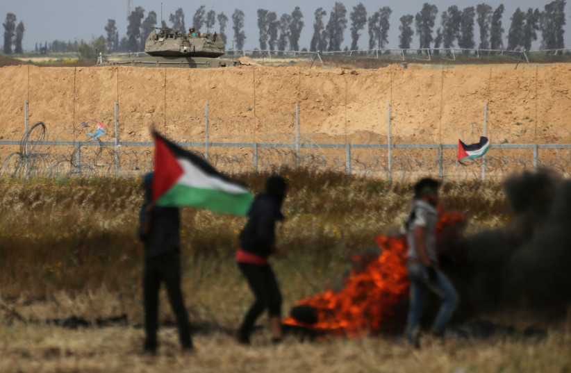 Israel soldiers ride on a military vehicle as Palestinian demonstrators are seen during clashes at a tent city protest at Israel-Gaza border, in the southern Gaza Strip (photo credit: IBRAHEEM ABU MUSTAFA/REUTERS)