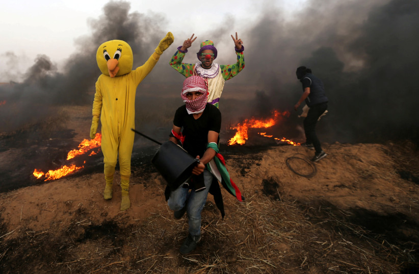Palestinians wearing costumes are seen at the clashes scene at Israel-Gaza border in the southern Gaza Strip April 5, 2018. (photo credit: IBRAHEEM ABU MUSTAFA / REUTERS)