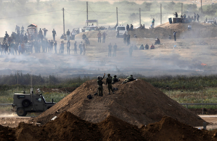 Israeli soldiers are seen next to the border fence on the Israeli side of the Israel-Gaza border, as Palestinians protest on the Gaza side of the border, Israel April 5, 2018. (photo credit: AMIR COHEN/REUTERS)