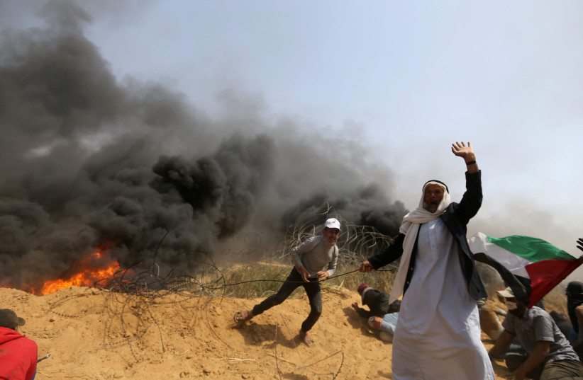 Palestinians remove a section of the border fence during Gaza protests (photo credit: IBRAHEEM ABU MUSTAFA/REUTERS)