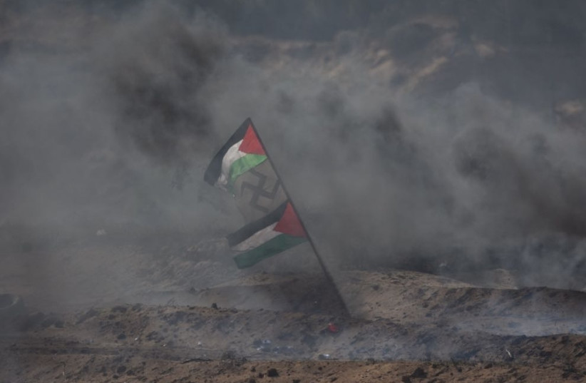 Palestinian flags flank a swastika in the midst of smoke during protests in Gaza (photo credit: IDF SPOKESMAN'S UNIT)