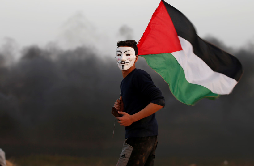 A Palestinian wears an 'Anonymous' mask and holds a Palestinian flag during protests in Gaza (photo credit: MOHAMMED SALEM/ REUTERS)